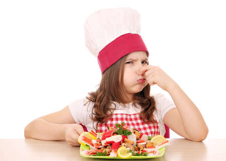 disgusted: little girl cook with seafood bad smell