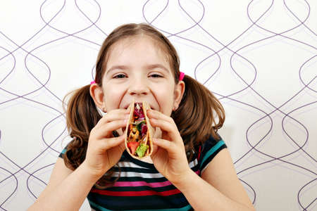 tacos: hungry little girl eating tacos Stock Photo