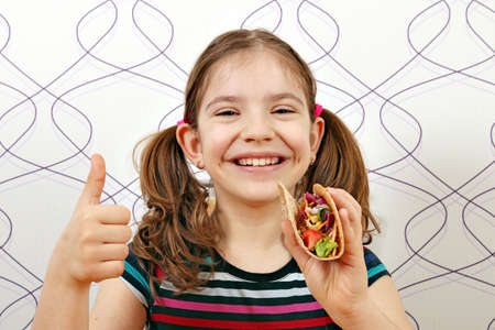 happy little girl with tacos and thumb up Foto de archivo