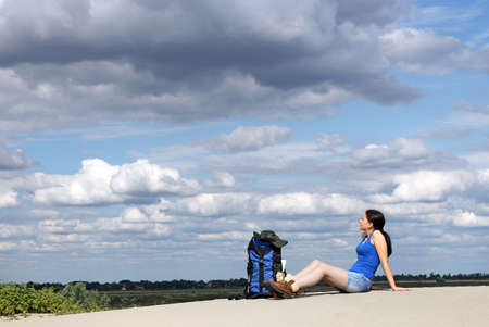 girl hiker sitting on the sand and rest photo