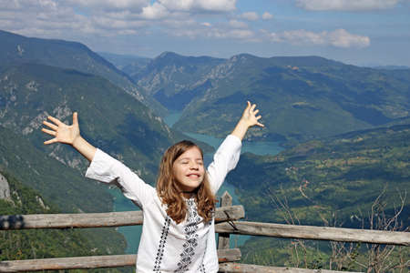 happy little girl with hands up on mountain Stock Photo