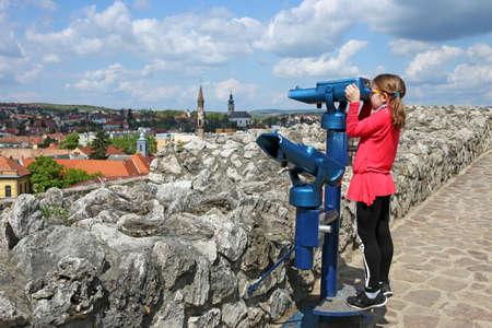 little girl looking through sightseeing binoculars on Eger  Stock Photo