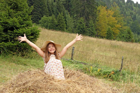 beautiful little girl with hands up enjoys nature summer season photo
