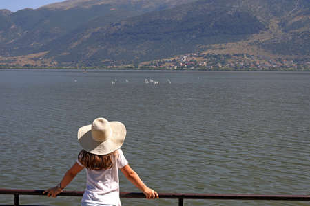 The girl watches the swans on the lake Ioannina Greece photo