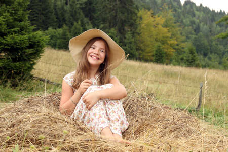happy little girl is sitting in the hay countryside summer season photo