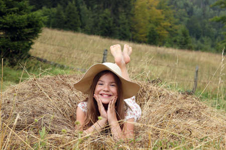 happy little girl lies in the hay summer season photo