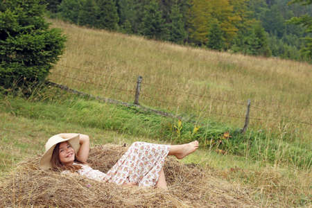 happy little girl lies in the hay  photo
