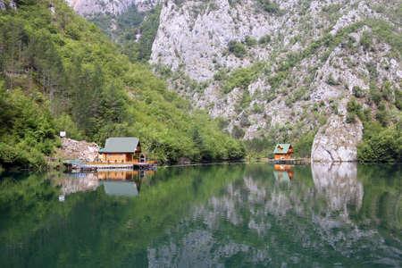 wooden cottages on river landscape