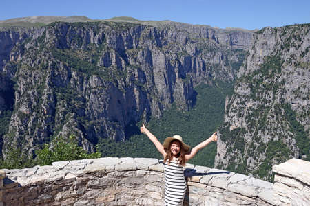 happy little girl with thumbs up on the viewpoint Vikos gorge Greece