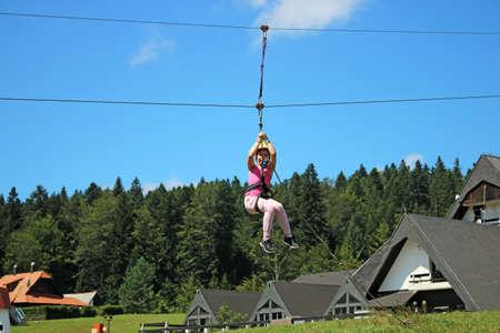 Little girl sliding on a zip line extreme park