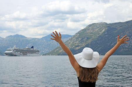 The girl welcomes the cruise ship Kotor bay Montenegro summer vacation Banco de Imagens