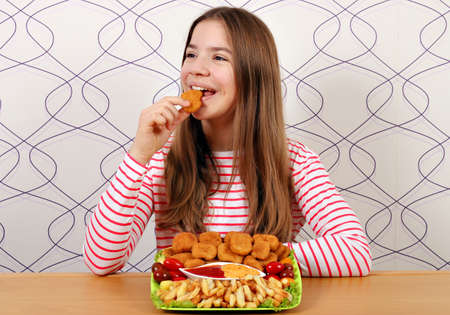 hungry teenage girl eats chicken nuggets fast food