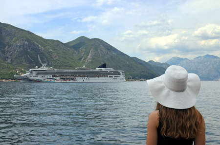 the girl looks at the cruise ship entering the Kotor bay Standard-Bild - 118590400
