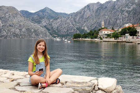 happy teenage girl with smart phone on summer vacation Kotor bay Montenegro