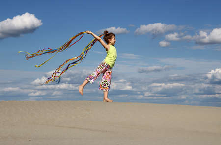 little girl play and waving with colorful ribbons summer season Imagens