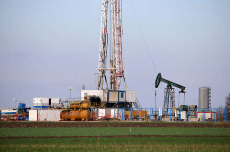 land oil drilling rig and pump jack in oilfield Stock Photo