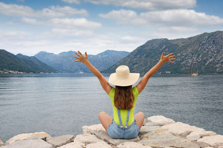 the girl with hands up enjoys a summer holiday Kotor bay Montenegro