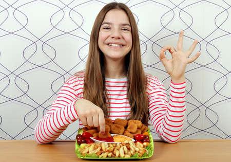 Adolescente heureuse avec de savoureuses pépites de poulet et signe de la main ok Banque d'images