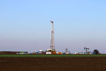Oil and gas drilling rig and pump jack in oilfield Banque d'images
