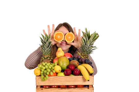 girl holding oranges in front of her eyes