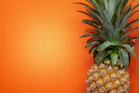 Fresh pineapple on a orange background. Reklamní fotografie