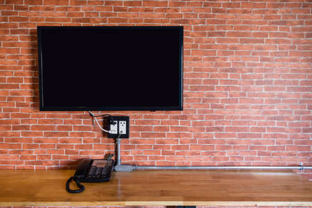 Flat screen television hanging at the brick wall with copy space in living room or bedroom Reklamní fotografie