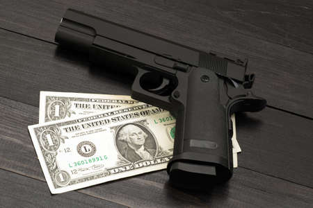 Black gun on banknotes. Concept of armed criminal offenses Stock Photo