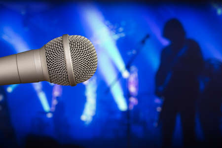 Stage microphone with a guitarist on the back blurry background. Rock star concept in blue tones. Stock Photo