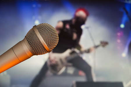 Stage microphone with a guitarist on the back blurry background. Rock star concept. Stock Photo