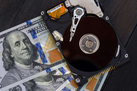 Disassembled hard drive and money on a wooden background. Concept of information safety
