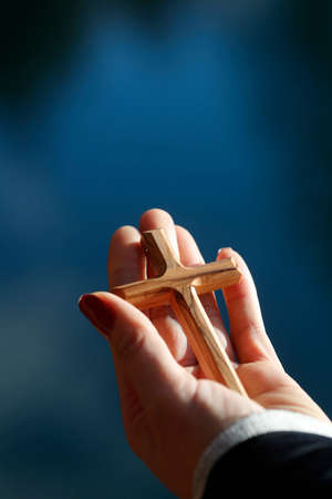 Christian wooden cross in hand. Faith and spirituality.