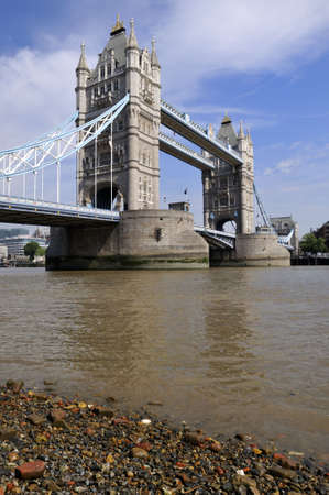 Tower Bridge at low tide over the River Thames, London, England, from the East, in summer, as the sun gets high in the sky photo