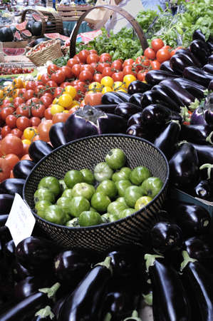 Bowl of tiger tomatoes on a market stall, in a sea of aubergines (egg plants) and red and yellow tomatoes Stock Photo - 3409664