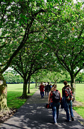 edinburgh: Students walking across the Meadows in Edinburgh, Scotland,on a sunny day in the shade of an avenue of trees
