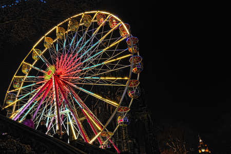 Big Ferris Wheel, East Princes Street Gardens, Edinburgh, Scotland, part of the Christmas and Hogmanay holiday attractions, at night.  The base of the Scott Monument is just visible in the background, as is the clock tower of the Balmoral Hotel.