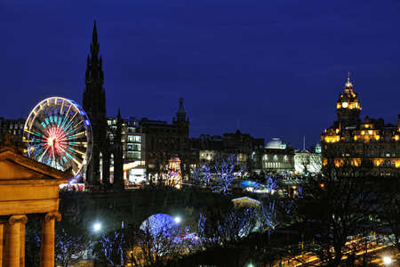 edinburgh: East Princes Street Gardens, Edinburgh, Scotland, with Christmas and Hogmanay holiday attractions, at night.  The Royal Scottish Musem, Big Wheel, Scott Monument and Balmoral make a colourful scene.