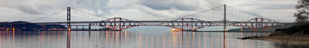 forth: Forth Road and Rail Bridges, Firth of Forth, from South Queensferry, just outside Edinburgh, Lothian, looking over to Fife, Scotland, illuminated on a still evening
