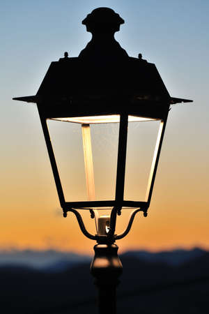 glassless retro electric street light, with a cobweb, sililhouetted against the sunset photo