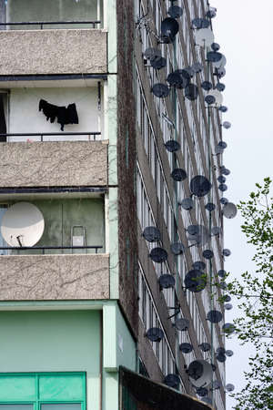deprivation: Rash of satellite dishes sprouting from a concrete block on the Aylesbury estate, Southwark, South London. Detail.
