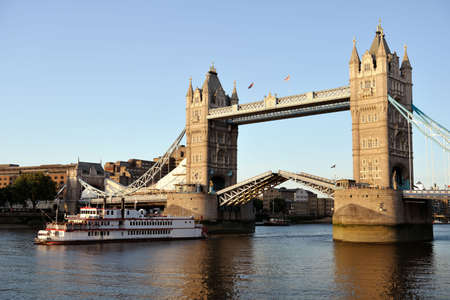 Replica of a 19th century Mississippi paddleboat passing though Tower Bridge, London, England, UK, Europe, at sundown.  (The bridge is being cleaned up for the Olympics.) photo