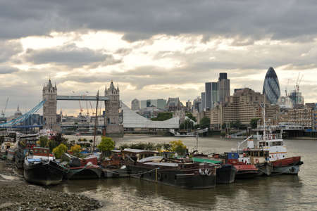 southwark: Houseboats moored on the south bank of the River Thames, Bermondsey, Southwark, London, England, UK, with Tower Bridge, being refurbished for the Olympics, in the background, and a dramatic stormy sky at the end of the day Stock Photo