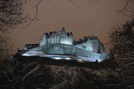 castle rock: Castillo de Edimburgo, Escocia, iluminado por la noche en la nieve de invierno