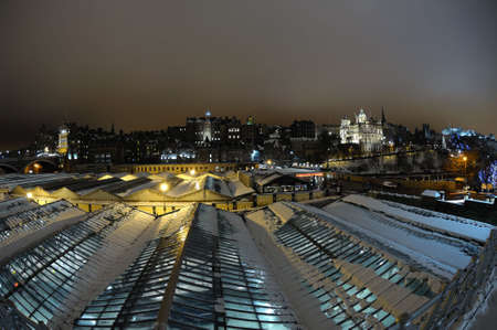 waverley: Old Town skyline, over the roof of Waverley railway station, Edinburgh, Scotland, UK, at night in winter with snow