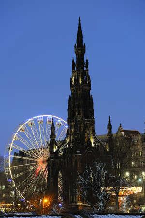 princes street: Scott Monument flanked by big Christmas Ferris Wheel and carousel in Princes Street Gardens, Edinburgh, Scotland, UK, at dusk
