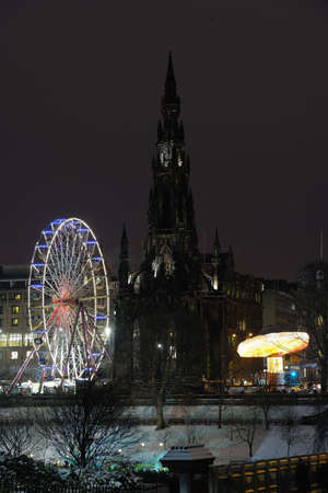 Scott Monument flanked by big Christmas Ferris Wheel and carousel in Princes Street Gardens, Edinburgh, Scotland, UK, at night photo