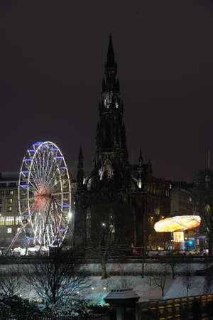 princes street: Scott Monument flanked by big Christmas Ferris Wheel and carousel in Princes Street Gardens, Edinburgh, Scotland, UK, at night Stock Photo