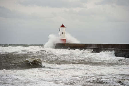breakwaters: Wave breaking over Berwick upon Tweed lighthouse, Northumberland, England, UK, on a stormy winter day