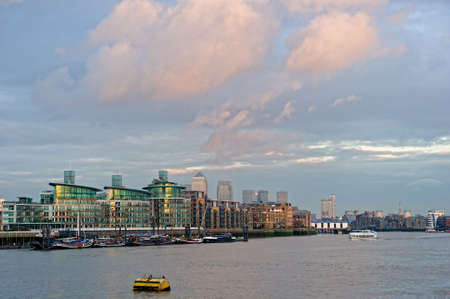 Typical luxury Thames riverside development, Wapping, East End, London, England, UK, with Canary Wharf in the background, at sunset photo