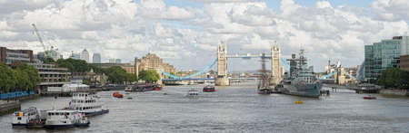 River Thames, Pool of London, looking towards Tower Bridge, London, England, UK, Europe, caught in a spot of sunlight on a cloudy summer afternoon photo