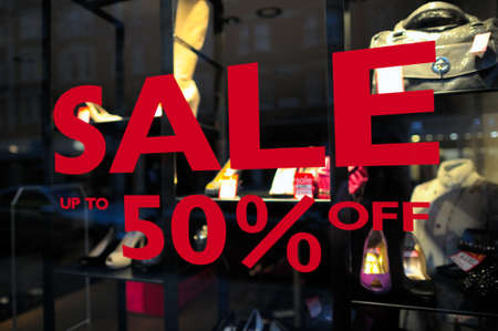 retailing: Sale (up to 50% off) sign in a fashion shop window. Selective focus on lettering.